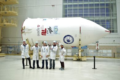 Team in front of Soyuz fairing